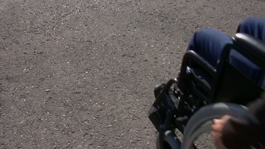 Man in a wheelchair pushes himself along entering frame on the right and moves across the frame. intro.