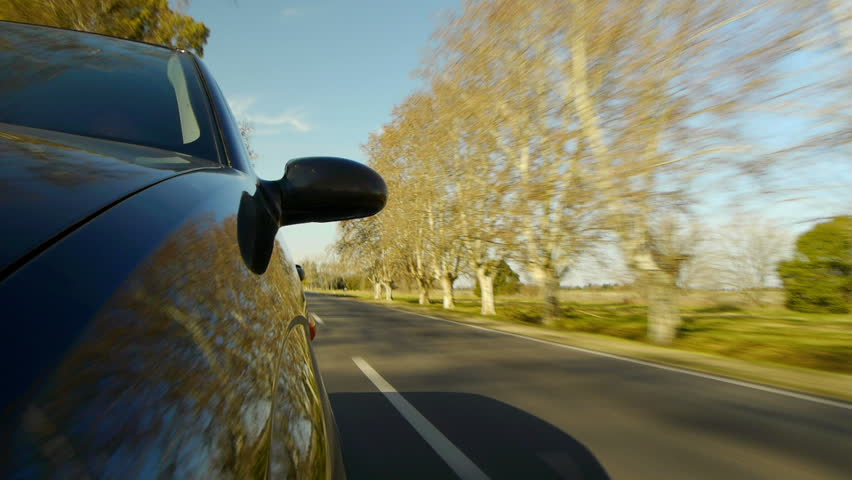 Driving a car, windshield reflection. Hood side reference. Mounted camera, front view. Black car ride. Country road, trees on the side, blue sky, day. Fast Speed / Time-Lapse. HD.