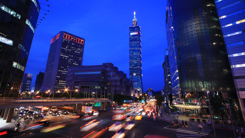 TAIPEI, TAIWAN - CIRCA JULY 2013: (Timelapse View) By the corner of busy Taipei street after working hours with Taipei 101 at back, circa JULY 2013 in Taipei, Taiwan.