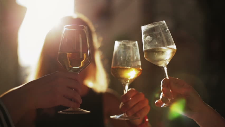 Women holding glasses of white wine making a toast at sunset