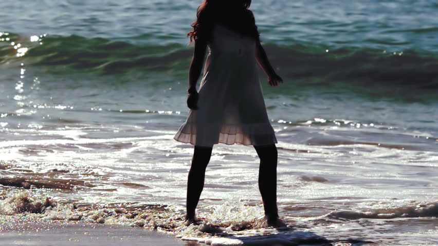Silhouette of woman revolving in waves in slow motion