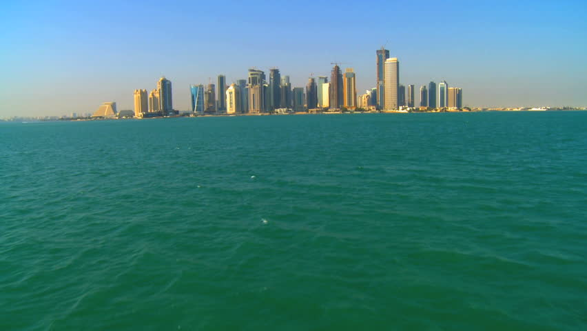 Approaching Persian Gulf modern cityscape buildings city Doha Qatar by boat