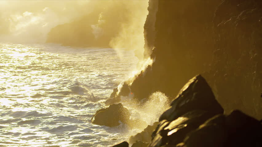 Steam from boiling lava flows beside jagged coastal rocks being cooled by crashing ocean waves at sunset Hawaii shot on RED EPIC
