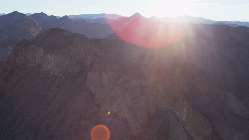 Aerial view with sun, lens flare, extreme mountain terrain nr Las Vegas, Nevada, USA