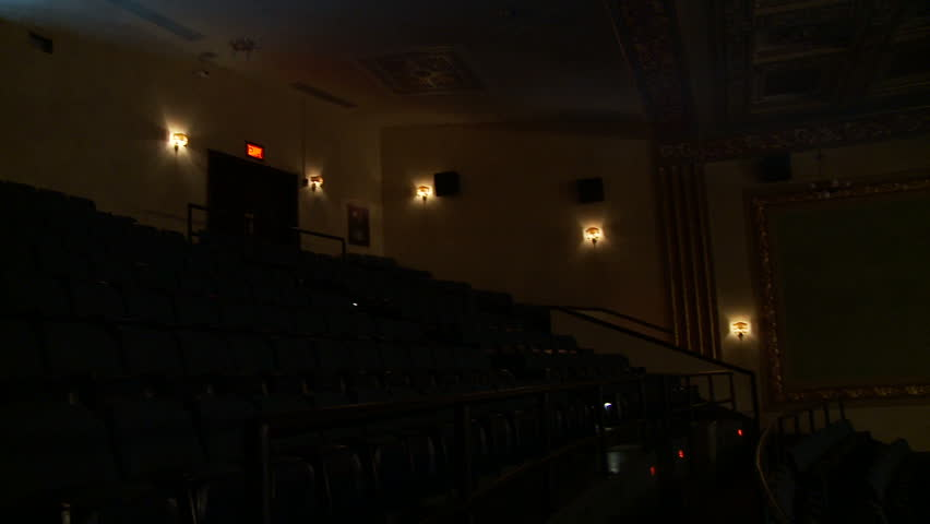 View of the light beam of a 35mm projector running in a semi-darkened movie theater.  Wall sconces are on, showing some dim details of the theater walls.  Little ambient light.
