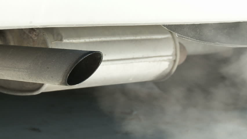 View of car exhaust pipe, emitting fumes, with details of car underside