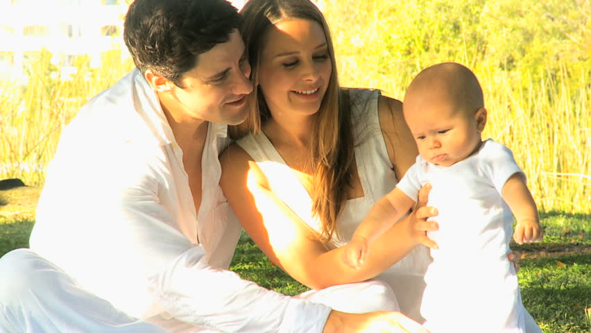 Loving young Caucasian parents holding happy baby son in sunshine outdoors | Shutterstock HD Video #4285823