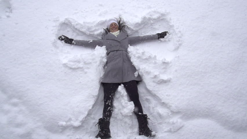 SLOW MOTION: Young woman making snow angels | Shutterstock Video #4308560