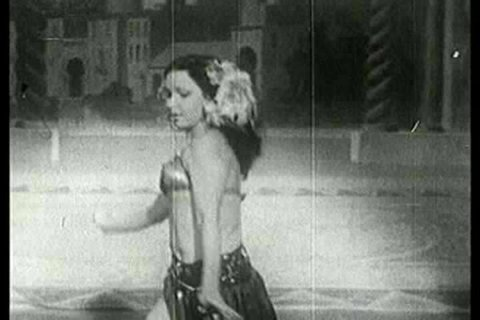 1930s - Rouhea Bey performs an exotic Arab strip dance at a burlesque club in the 1930s as part of this stag film.