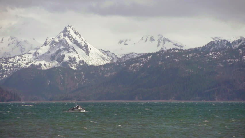 Small fishing boat cuts through storms waves on Kachemak Bay in Alaska