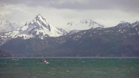 Small fishing boat cuts through storms waves on Kachemak Bay in Alaska