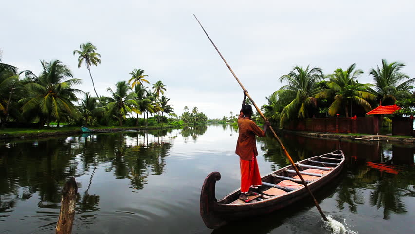 KERALA, INDIA - SEPT 14 2012: Man rowing a boat in a lake, Alleppey, Kerala, India, 14/09/2012