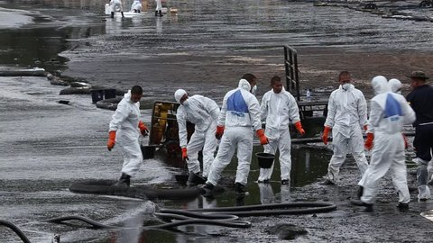 RAYONG, THAILAND - JULY 31, 2013: Workers wearing biohazard suits pass a pail full of spilled crude oil as cleaning operations from a beach of Samet Island on July 31, 2013 in Rayong, Thailand.