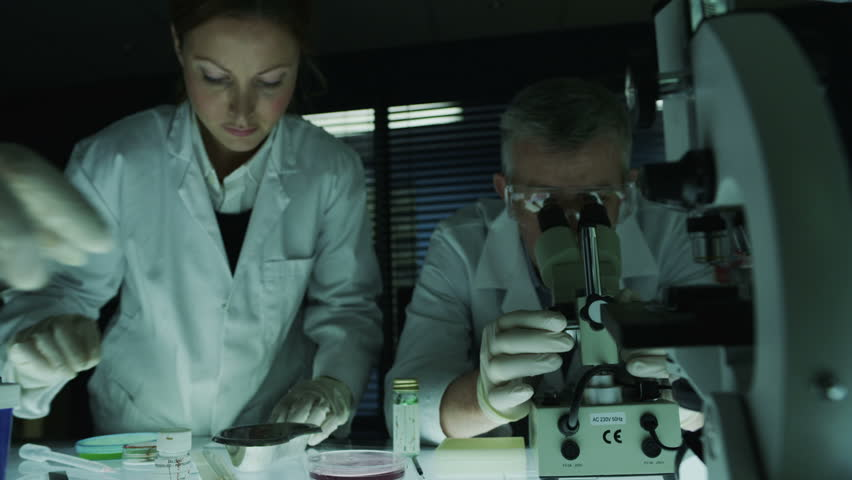 A mature male scientist or medical researcher is working in a dark laboratory, teaching a young team of students or trainees. In slow motion.