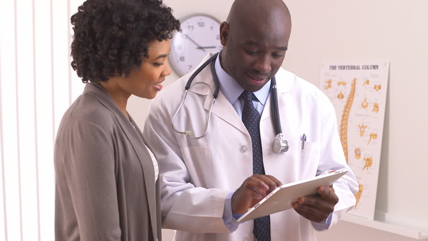 African American doctor using tablet pc with female patient