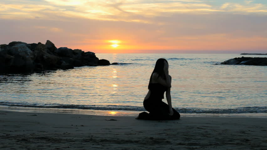 Woman feeling lonely and desperate on the beach at sunset