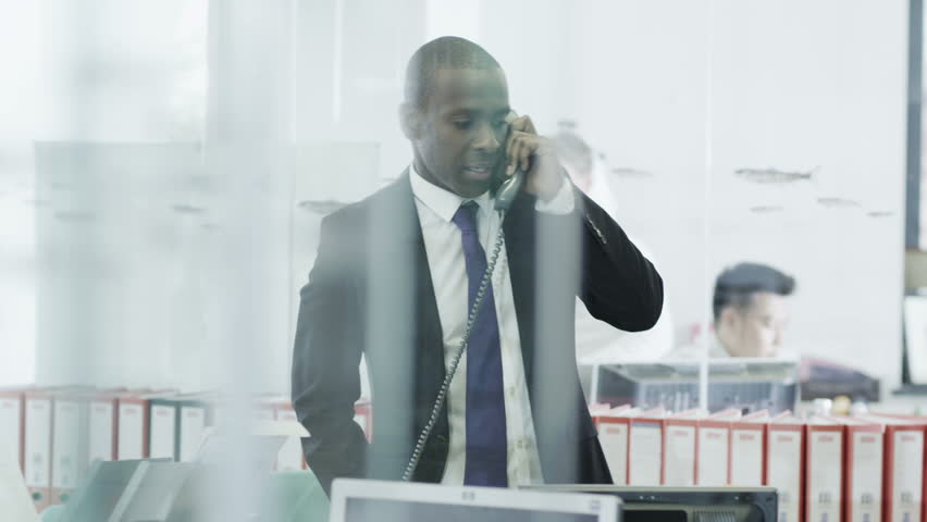 Confident and mature black businessman takes a call in an informal but busy modern office. In slow motion.