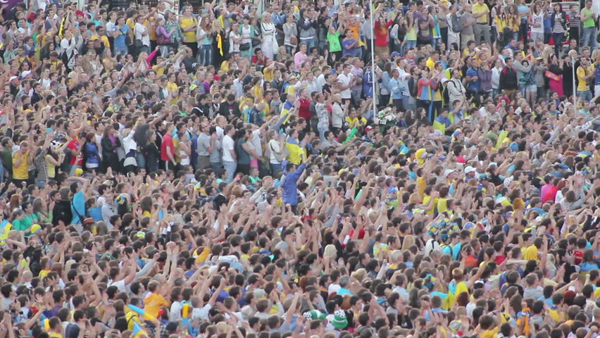 KIEV, UKRAINE - JUNE 16: Football fans on the city square during the Euro 2012 tournament. Football fans celebrate a goal. Unrecognizable crowd of people watching soccer