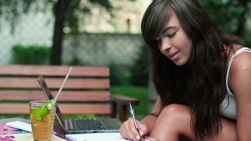 Female student working with laptop and notebook in the park