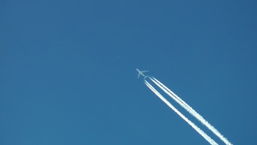 A Jet plane cuts across a perfectly clear blue sky, leaving a drifting vapor