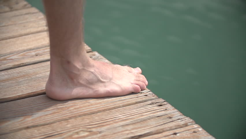 Foot steps up to the edge of a doc in beautiful super slow motion.