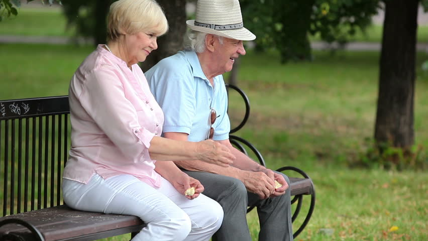 Retired couple enjoying peaceful day feeding pigeons in the park
