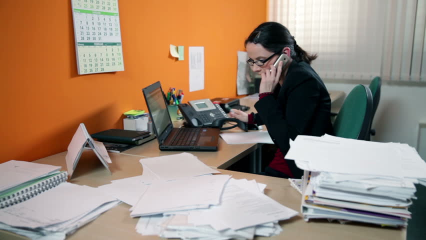 Business woman in office on the phone searching for documents
