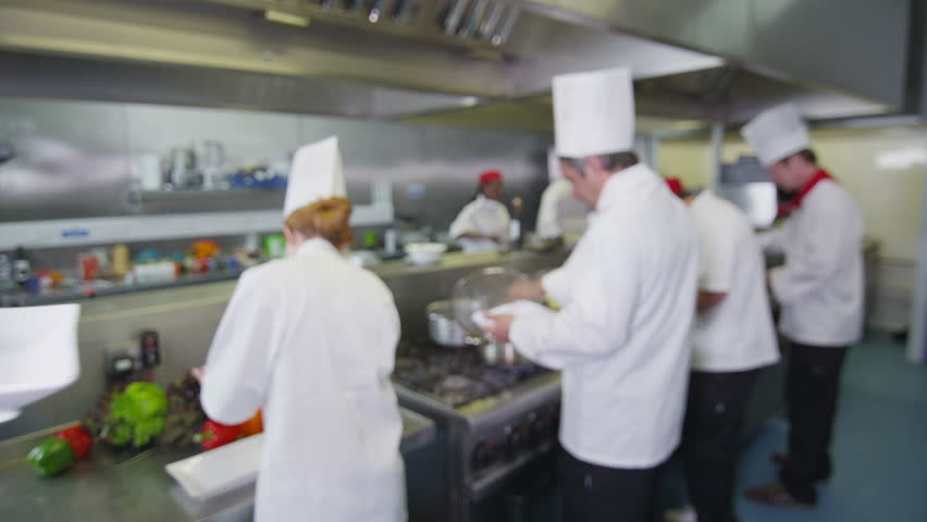 Waitress collects her order from the chef in a busy hotel or restaurant kitchen. In slow motion.