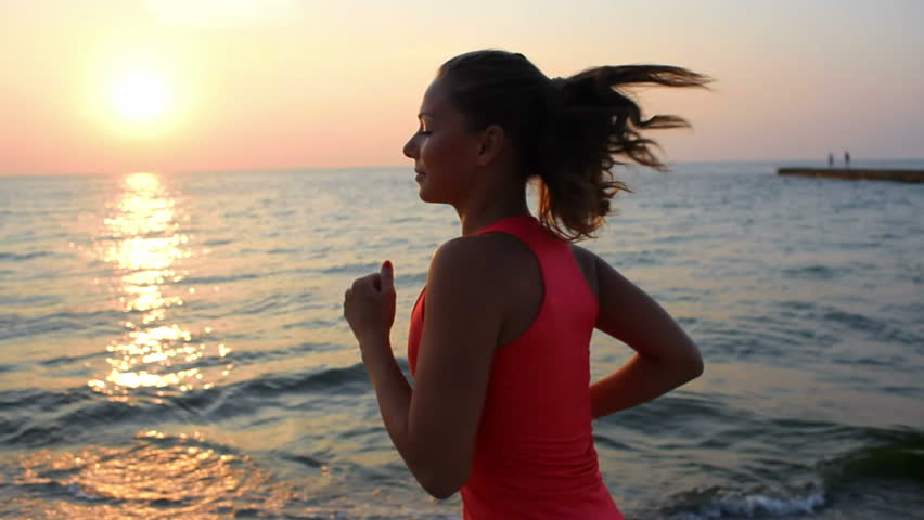 A young woman with a slender figure is engaged in gymnastics at sea at sunrise. She makes a run along the sea coast. sequence camera stabilizer shots.  | Shutterstock HD Video #4470491