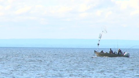 Fishermen trolling for fish on Lake Superior in small boat.