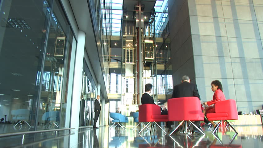 Time lapse modern business office as people rush past camera. Large corporate building and staff working. Businessman and businesswoman shaking hands.