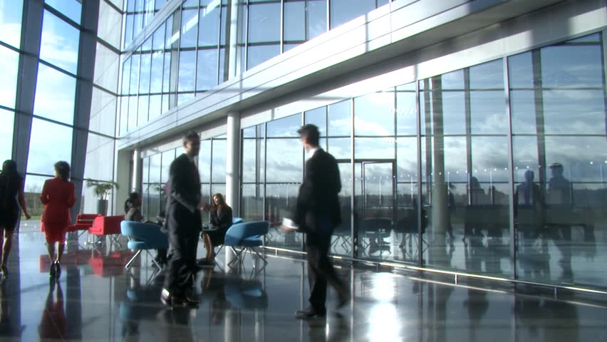 corporate office window 4k businessmen talking as they walk through lobby of corporate