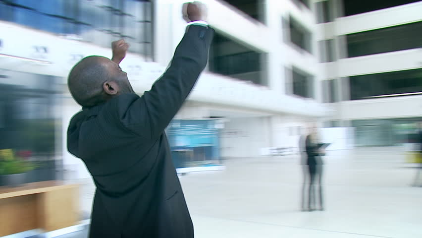 Ecstatic businessman celebrates his success and throws papers and documents into the air in the middle of a busy contemporary office building. High quality HD video footage
