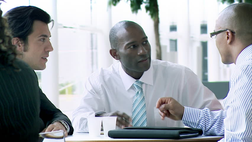 Track and Dolly HD. Busy working office. Multiple actors in business pose. Multiracial businessmen conducting a meeting in relaxed atmosphere. High quality HD video footage