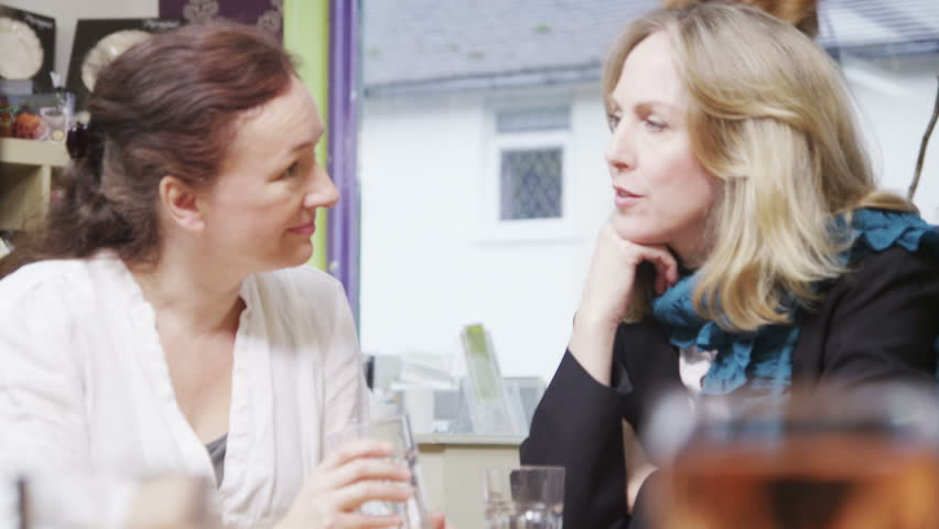 Attractive mature female friends enjoy a good gossip over drinks in a small cafe or wine bar. In slow motion.