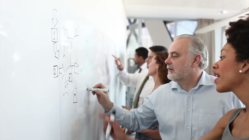 Business people brainstorming ideas on a whiteboard in a large corporate office. Attractive workers building a plan together. A teamwork scene with lovely DOF. High quality HD video footage | Shutterstock HD Video #4493294
