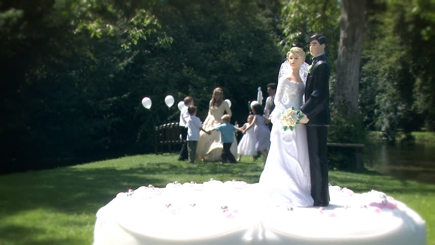 Bride and groom cake topper and children playing in the background at summer outdoor wedding.