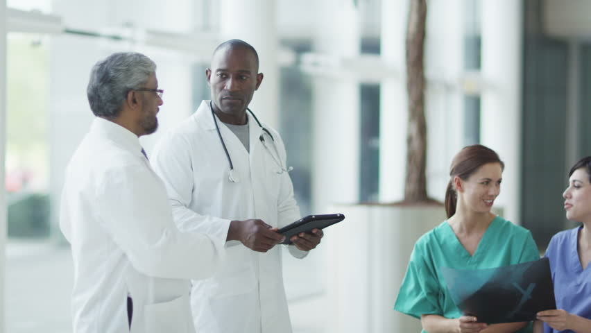 Doctors, nurses and surgeons in group meeting. A touch screen device is central to the discussion. A hospital ward or waiting area where patients can by seen by doctors and nursing staff. | Shutterstock HD Video #4503689