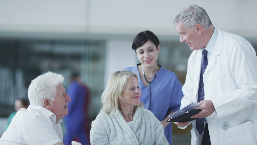 Woman comforted by caring medical staff. Assisting people when life throws unexpected obstacles in your way. A hospital ward or waiting area where patients can by seen by doctors and nursing staff. | Shutterstock HD Video #4503788