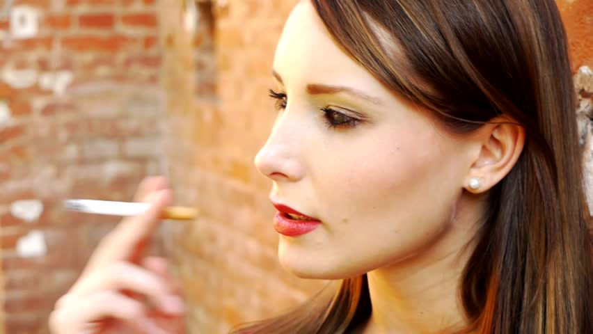 HD1080p50 Young woman smoking a cigarette outdoor