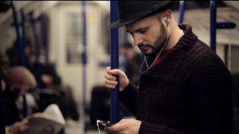 man listening music on a tube train standing
