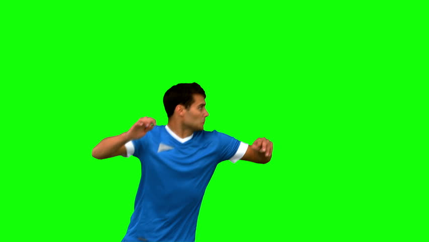Handsome man heading a football on green screen in slow motion