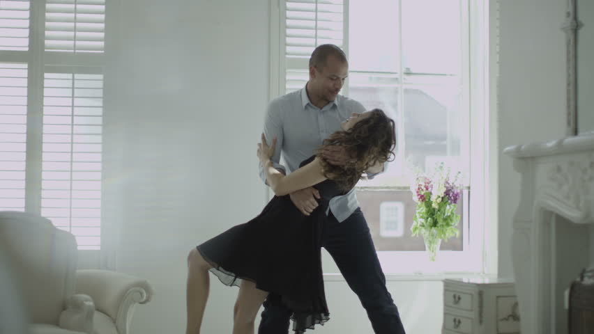 Happy and attractive young couple in love dance together in their stylish apartment. In slow motion.