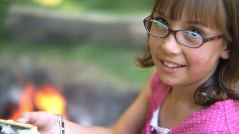 Girl eating a smore by campfire