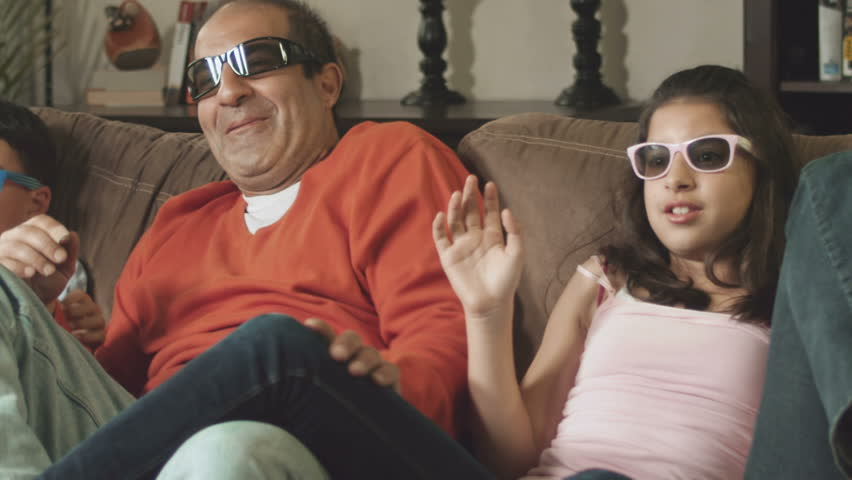 A family spending tie together watching a 3D movie. Medium shot in slow motion