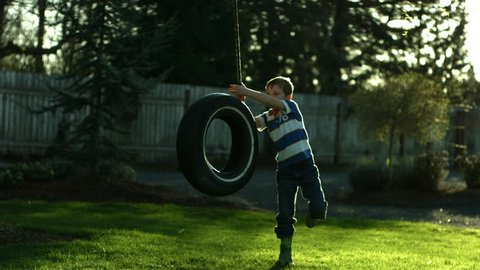 Boy playing on tire swing, slow motion