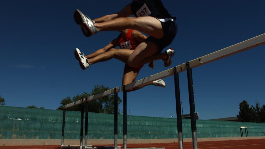 Athletes jump over hurdles, slow motion