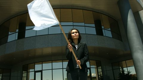 Businesswoman in front of office building waving white flag