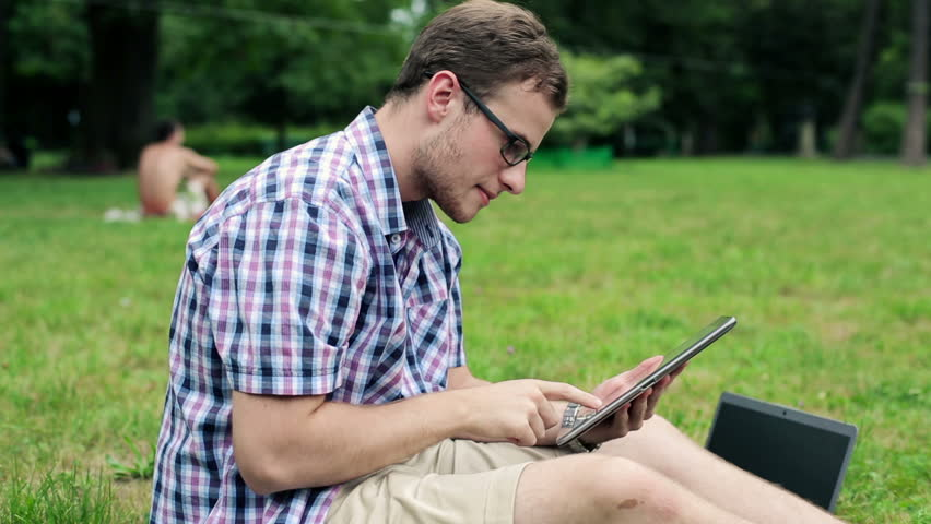 Young male student with tablet computer in the park