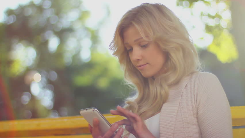 Woman types sms smiles sending message, daytime park bench